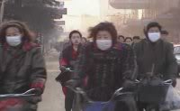 Lots of Chinese cyclists, some wearing masks against the smog