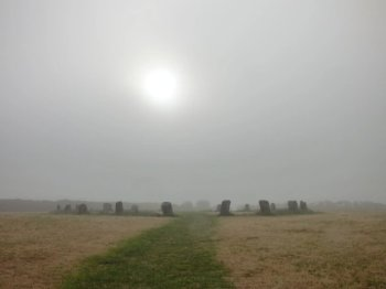 A pale sun piercing the mists above a green path through a golden field, leading into the centre of a circle of stones