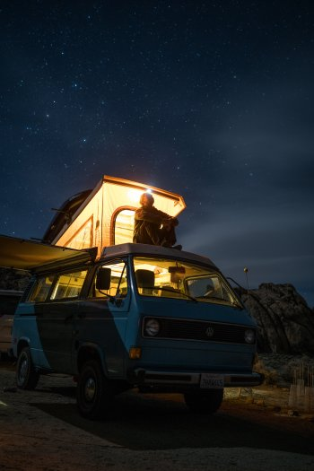 Man sitting on van at night looking up into a starry sky