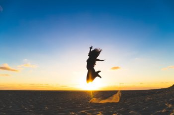 Woman leaping on sand at sunset