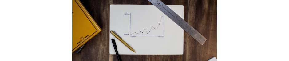 An upward-trending graph with writing implements and a rule